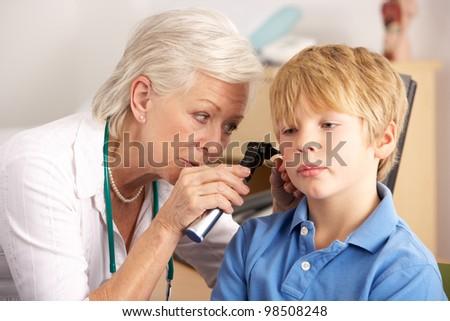 British GP examining young boy's ear - stock photo