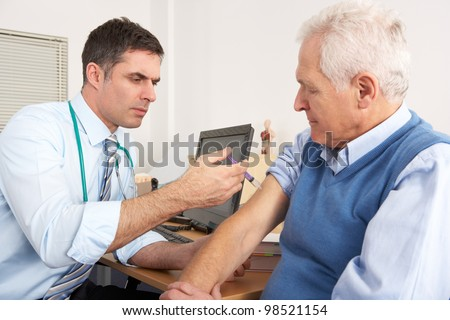 British GP injecting senior man in surgery - stock photo