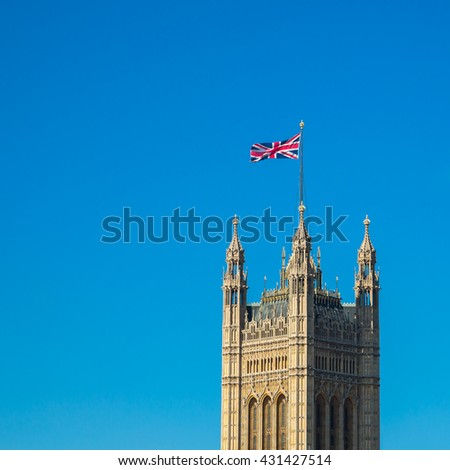 British national flag on top of Parliament building with blue sky - stock photo