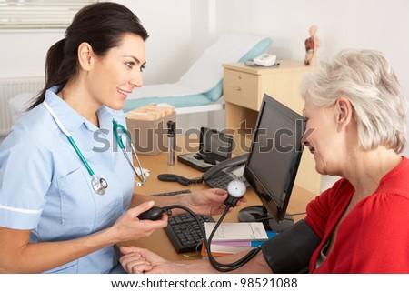 British nurse taking senior woman's blood pressure - stock photo