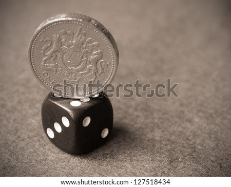 British One pound coin balanced on top of a black dice - stock photo