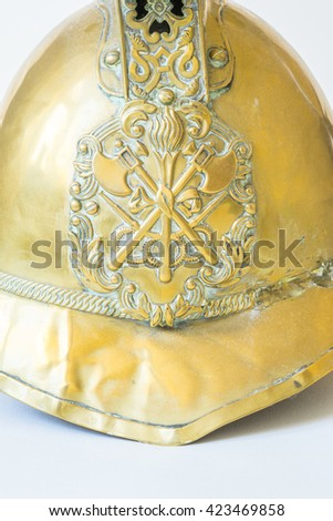 British Other Ranks Merryweather Brass Fire Helmet, used during the blitz, Second World War, with consequent damage. Close up of badge showing crossed axes,torch and hose pipes - stock photo