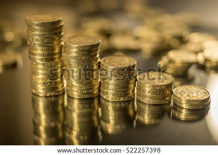British pound coins neat stacks up close macro studio shot against a shiny reflective black background
