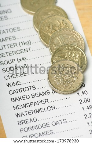 British Pound Coins on a Receipt for Food Shopping as a concept for rising prices and the cost of living. - stock photo