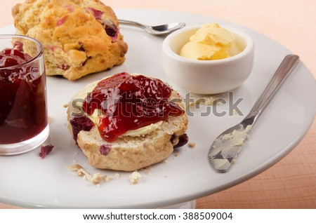 british scone with strawberry jam and butter on a cake stand