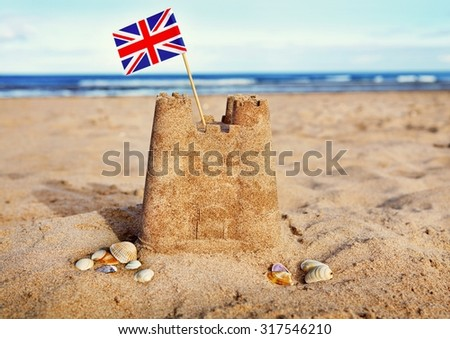 British Seaside traditional sand castle on the beach with Union Jack flag and shells - stock photo
