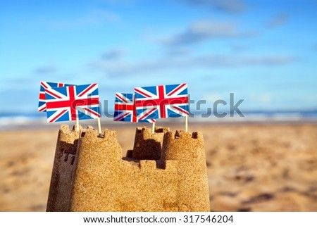 British seaside traditional sand castle on the beach with Union Jack Flags - stock photo
