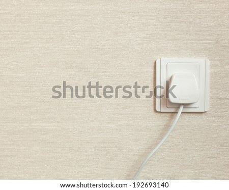 British Standard BS 1363 three pin power plug in a wall socket  - stock photo