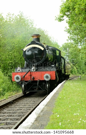 british steam train arriving at a rural platform - stock photo
