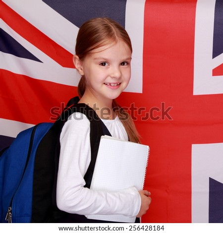 British young schoolgirl smiling on the background of the flag of England - stock photo