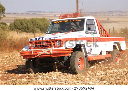 BRITS, SOUTH AFRICA - July 11:  Africa-Offroad Racing Rally,  on July 11, 2015 at Koster, North West Province, South Africa.  Drifting white Toyota Landcruiser truck kicking up dust on turn ar rally.  - stock photo