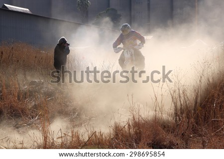 BRITS, SOUTH AFRICA - July 11:  Africa-Offroad Racing Rally,  on July 11, 2015 at Koster, North West Province, South Africa.  Motorbike airborne over bump in dust on sand track during rally race. - stock photo