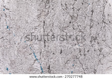 Brittle texture of a weathered ancient block of stone in an exterior load-bearing wall. Pale gray and light beige color. Black fissures, cracks and veins. Some blue paint stains. Flat background. - stock photo