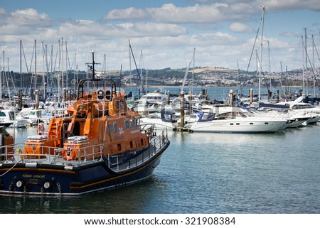BRIXHAM, DEVON, UK. JULY 30, 2015. Brixham lifeboat with yachts and boats in the harbour, Brixham, Devon, UK. - stock photo