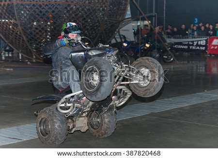 BRNO, CZECH REPUBLIC-MARCH 4,2016: Stuntman riding a quad bike, ATV during stunt show on International Fair for Motorcycles  on March 4,2016 in Brno in Czech Republic