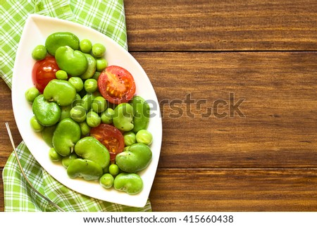 Broad bean, green pea and cherry tomato salad, photographed overhead on dark wood with natural light