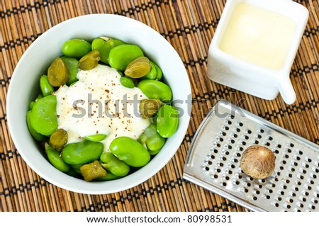 Broad beans and capers with creamy nutmeg sauce - stock photo