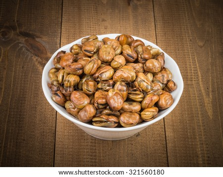 Broad beans in white bowl  on wooden table - stock photo