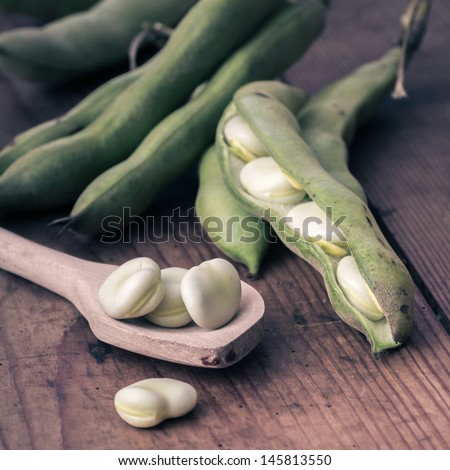 Broad Beans on a wooden Table with Spoon - stock photo