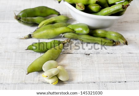 BROAD BEANS OVER WHITE WOOD - stock photo