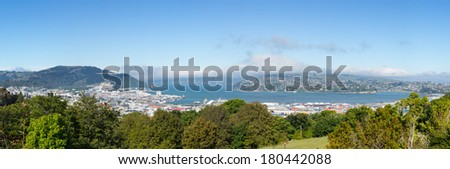 Broad panoramic landscape of the Otago Peninsula and Bay with the city of Dunedin in the foreground and clouds hanging over the mountains - stock photo