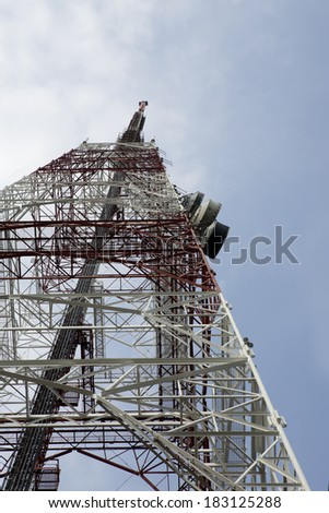 Broadcast transmission towers atop a hill in Singapore. The image shows the tower shot against a cloudy blue sky from directly below. - stock photo