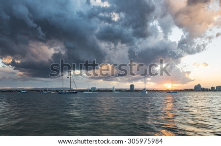 Broadwater Seaway After a Storm With Sailboats and Dramatic Clouds During a Golden Sunset, Southport, Gold Coast, Queensland, Australia - stock photo