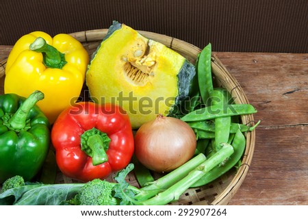 broccoli and bell pepper, pumpkin fresh vegetables in pannier on wood table - stock photo