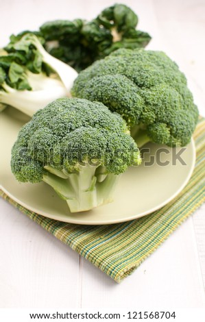 Broccoli and bok choy on green plate vertical - stock photo