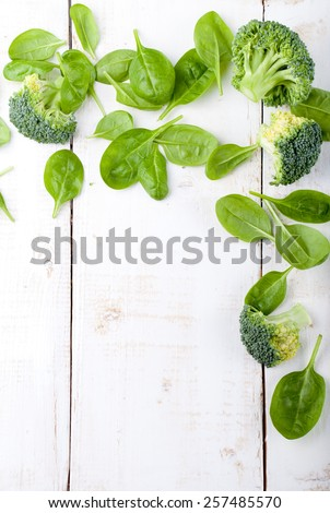 Broccoli, baby spinach and green beans salad in ceramic bowl with olive oil on a white wooden background. Copy space. - stock photo