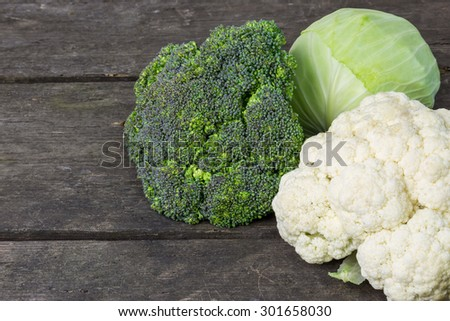 Broccoli, cauliflower and cabbage on a rustic background - stock photo