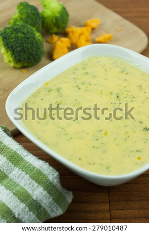 Broccoli cheese soup in a white bowl on a wooden table.