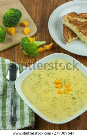 Broccoli cheese soup in a white bowl with a grilled cheese sandwich on a wooden table.