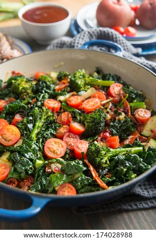 Broccoli, Cherry Tomatoes, Italian Kale, and Onions Sauteed in Skillet for Healthy Meal - stock photo