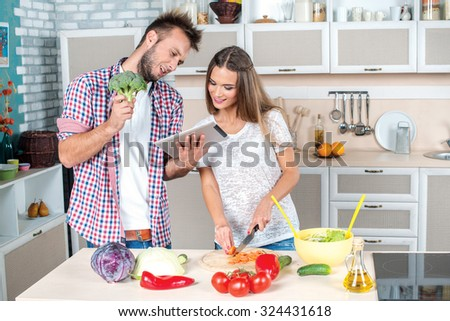 Broccoli for salad. Young and beautiful couple in love food prepared according to the recipe on the tablet while they are preparing breakfast in the kitchen.