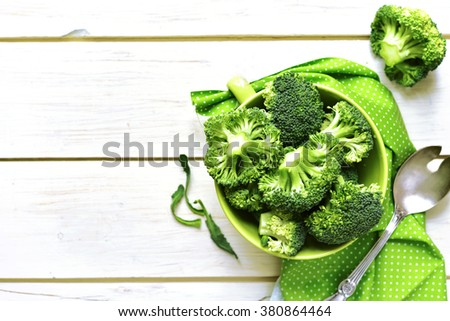 Broccoli in a ceramic bowl on a white wooden table.Top view. - stock photo
