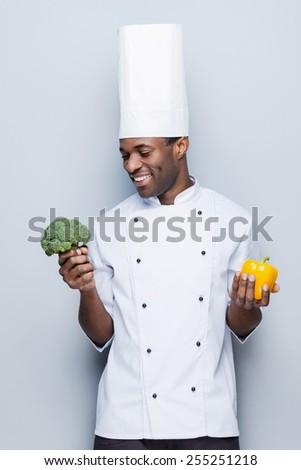 Broccoli or pepper? Cheerful young African chef in white uniform holding pepper in one hand and broccoli in another while standing against grey background - stock photo