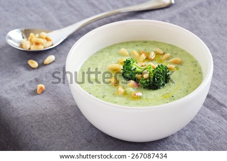 Broccoli-potato vegetarian soup with pine nuts and broccoli topping.Selective focus.