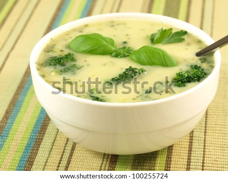 Broccoli soup in the white bowl decorated with basil leaf