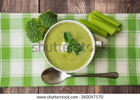 Broccoli soup puree with mint and ricotta cheese on the dark wooden background. Top view. - stock photo
