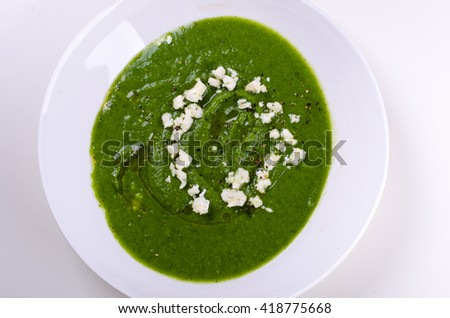 Broccoli soup with mint and feta cheese on white background