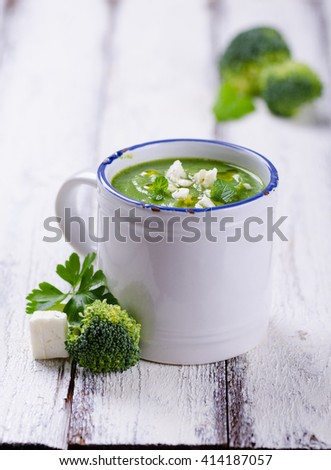 Broccoli soup with mint and feta cheese on white wooden background
