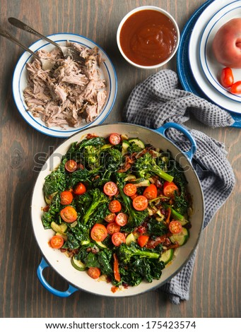 Broccolini, Cherry Tomatoes, Italian Kale, and Onions Sauteed in Skillet for Healthy Meal Served with Slow Cooked Pulled Pork - stock photo