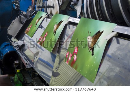 Brochure and magazine stitching process. Close-up of the offset conveying process of a full-automatic stitching unit. - stock photo