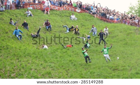 BROCKWORTH - MAY 25: Revellers join the traditional cheese rolling races on May 25, 2015 in Brockworth, UK. Thousands attended unofficial annual event which dates back to at least 19th century. - stock photo