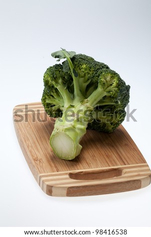 brocolli on the cutting board on the white background - stock photo
