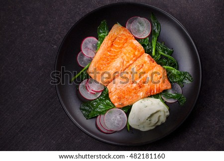 Broiled salmon with radish and spinach, served on black plate. View from above, top studio shot
