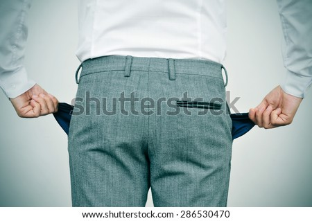 broke businessman wearing white shirt and grey trousers shows his empty pockets, seen from behind - stock photo