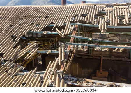 broken and destroyed roof of an old abandoned industry - stock photo
