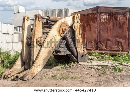Broken and salvaged large yellow industrial machine mechanical grab frontloader at a scrap breakers yard in non-working condition. The lifting section has been stripped of working parts.